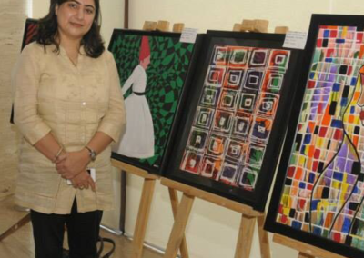 artist standing near her paintings